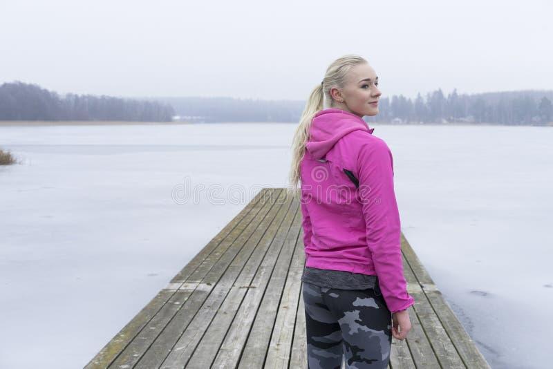 Muchacha caucásica sueca europea rubia hermosa de la aptitud en el lago del hielo fotografía de archivo
