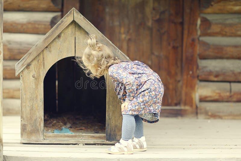 Muchacha cerca de la casa de perro imagen de archivo