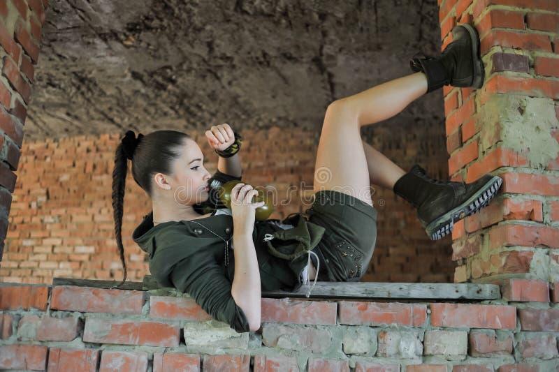 Muchacha cerca de la pared de ladrillo en estilo militar fotografía de archivo
