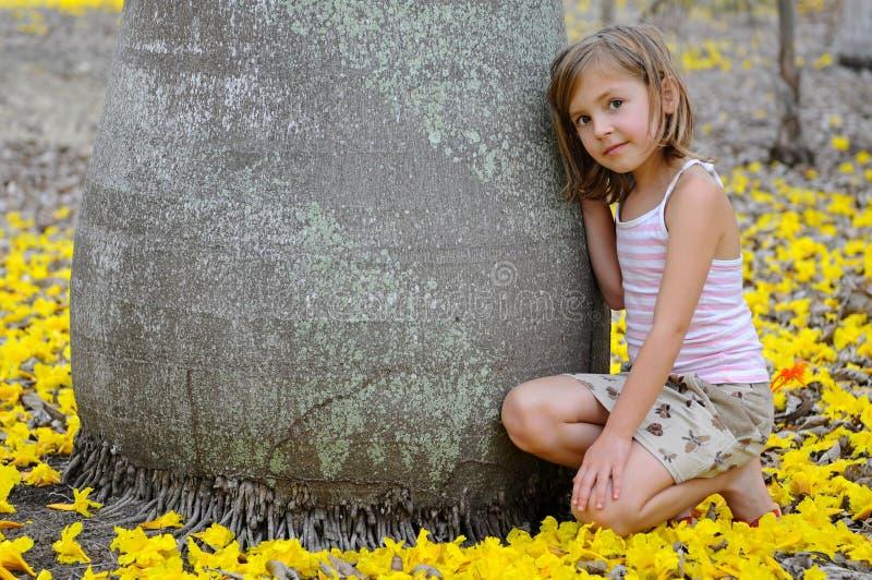Muchacha cerca del árbol grande rodeado por la flor amarilla imagen de archivo