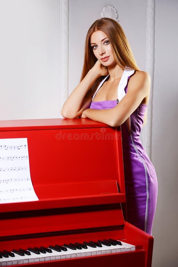 Muchacha cerca del piano imagenes de archivo