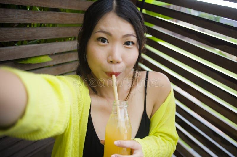 Muchacha china asiática atractiva y feliz joven que se divierte en el jardín al aire libre que bebe el zumo de naranja sano con l foto de archivo libre de regalías