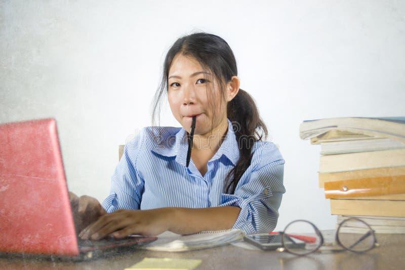 Muchacha china asiática eficiente hermosa y feliz joven del estudiante que trabaja en proyecto con la sentada confiada sonriente  imágenes de archivo libres de regalías