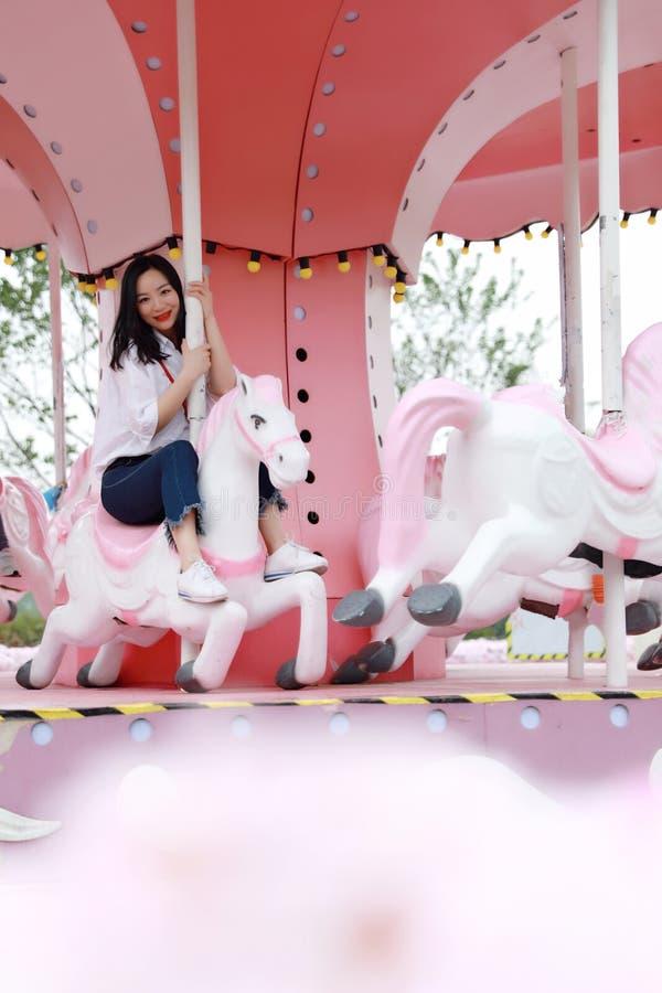 Muchacha china asiática feliz de la mujer en el tiovivo en un parque de atracciones imagen de archivo