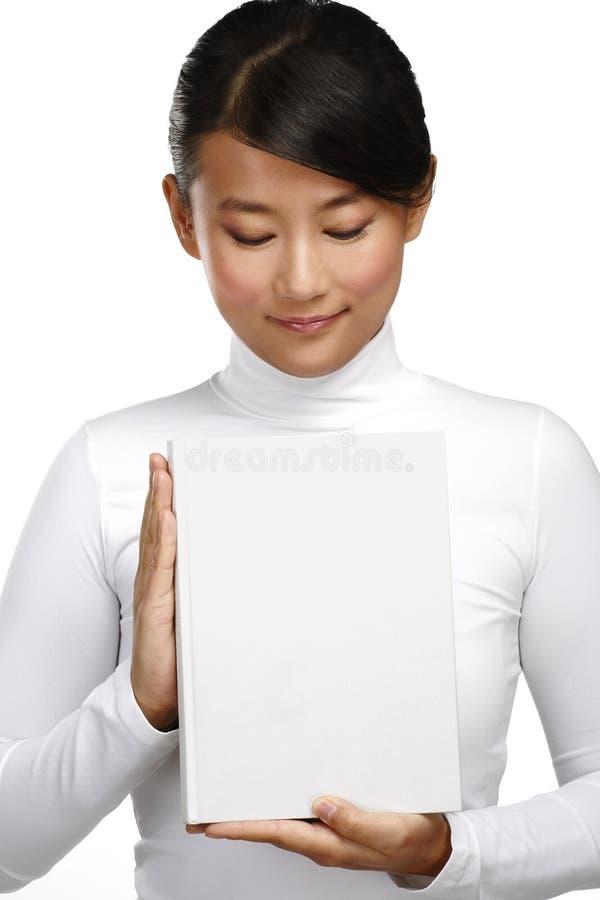 Muchacha china asiática hermosa que muestra un libro en blanco fotografía de archivo libre de regalías