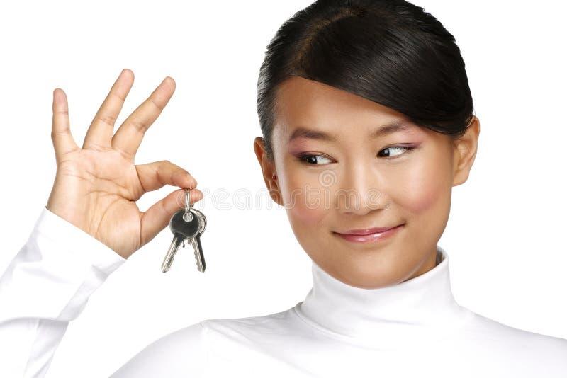 Muchacha china asiática linda que muestra llaves planas imágenes de archivo libres de regalías