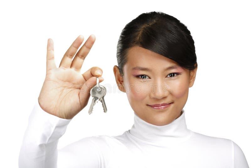 Muchacha china asiática linda que muestra llaves planas imagen de archivo libre de regalías