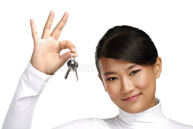 Muchacha china asiática linda que muestra llaves planas foto de archivo libre de regalías