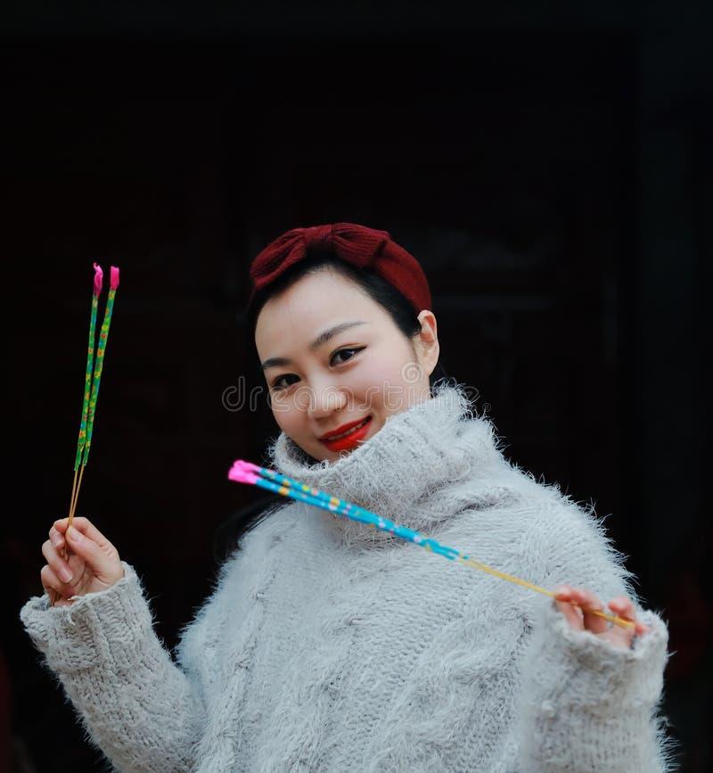 Muchacha china asiática que sostiene no todavía el fuego artificial del burningsparkler con la mano Morenita, mirando foto de archivo