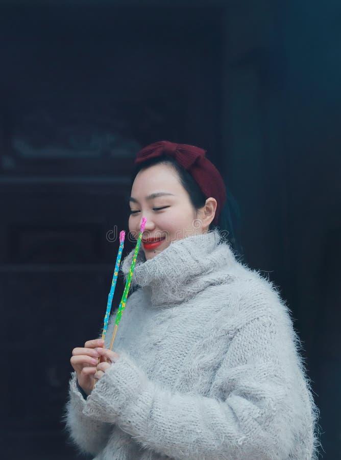 Muchacha china asiática que sostiene no todavía el fuego artificial del burningsparkler con la mano Morenita, mirando foto de archivo libre de regalías