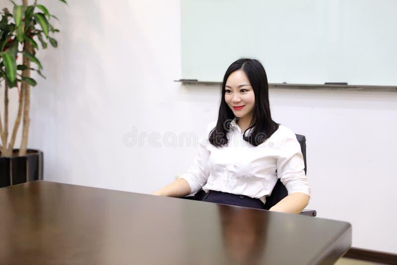 Muchacha china de la mujer de la señora de la oficina de Asia en lugar de trabajo de pensamiento del traje del empleo del negocio imagen de archivo libre de regalías