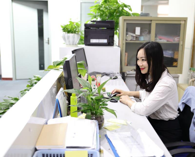 Muchacha china de la mujer de la señora de la oficina de Asia en la mirada de la sonrisa del trabajo en el lugar de trabajo elega fotografía de archivo libre de regalías