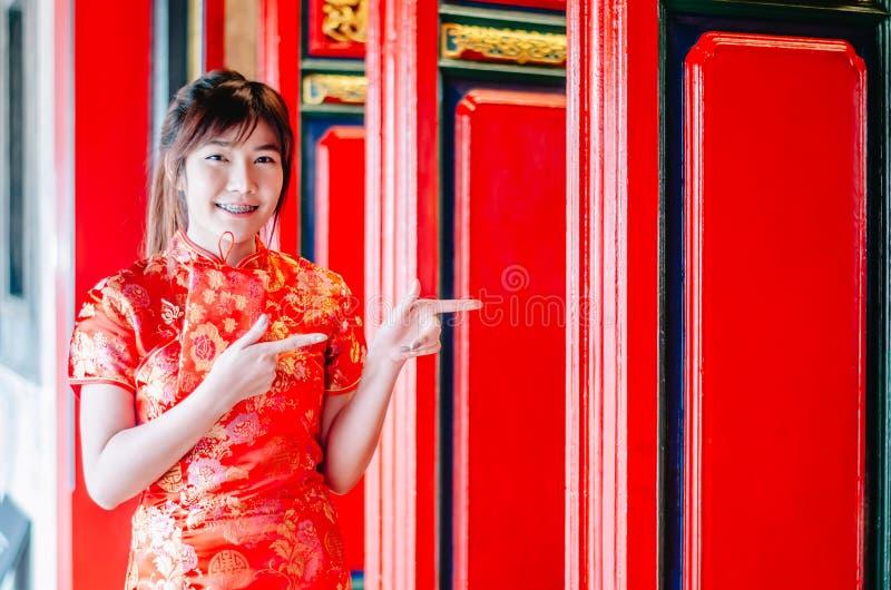 Muchacha china en cheongsam chino tradicional que señala en el templo de China e introducir algo a usted imagenes de archivo