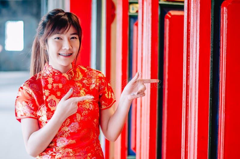Muchacha china en cheongsam chino tradicional que señala en el templo de China e introducir algo a usted imágenes de archivo libres de regalías