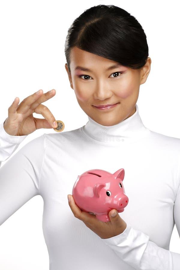 Muchacha china feliz hermosa que muestra un piggybank imagen de archivo
