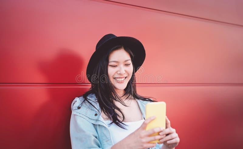Muchacha china feliz que usa el teléfono móvil al aire libre - mujer social asiática del influencer que se divierte con los nuevo fotografía de archivo