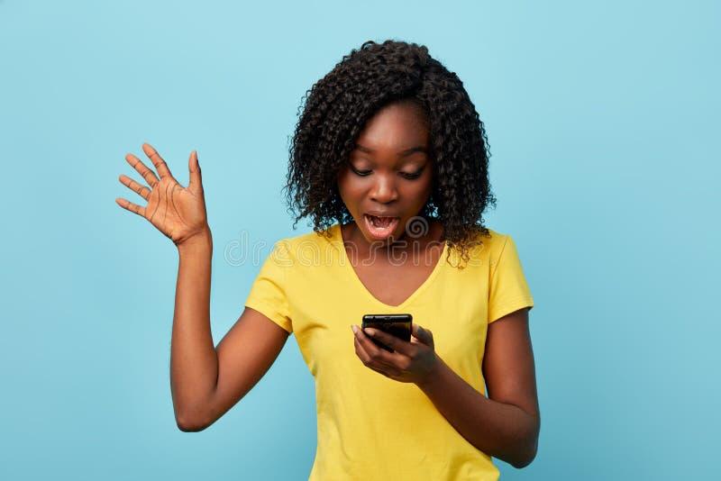 Muchacha chocada atractiva con smartphone en su información de lectura de la mano fotografía de archivo