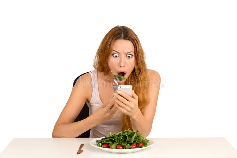 Muchacha chocada que come la ensalada verde que mira el teléfono que ve malas noticias de última hora imagen de archivo