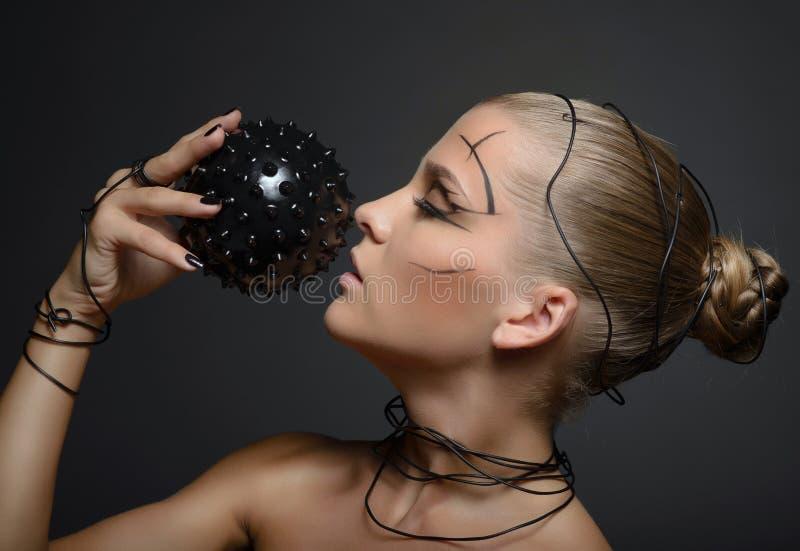 Muchacha cibernética hermosa con la bola espinosa negra fotos de archivo