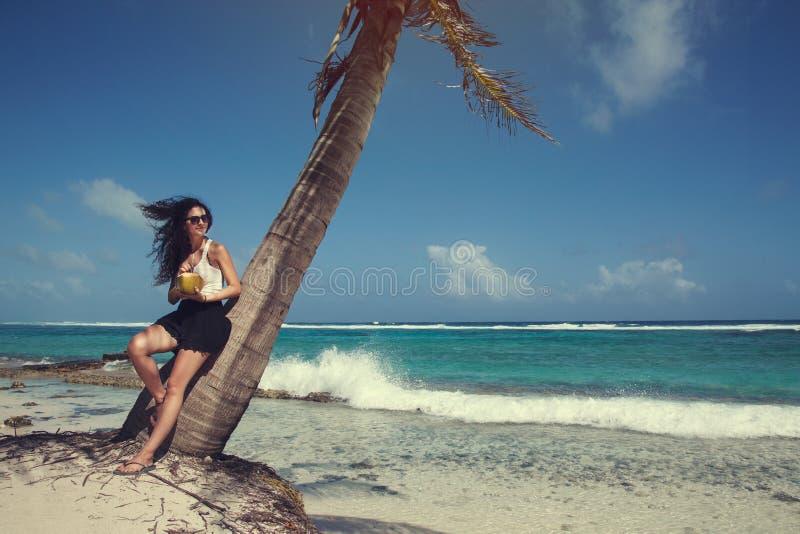 Muchacha colombiana en vacaciones debajo de una palmera foto de archivo