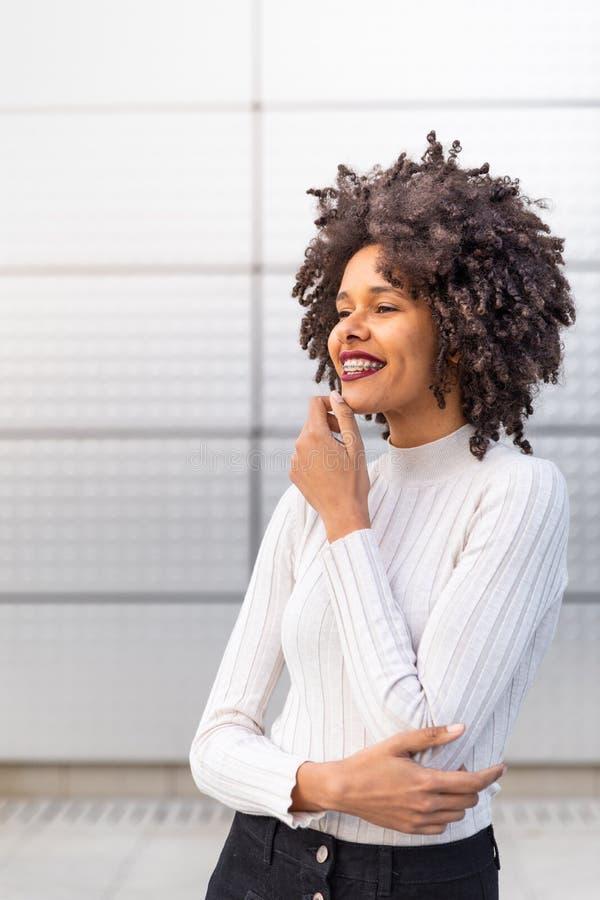 Muchacha coloreada sonriente con el pelo rizado foto de archivo