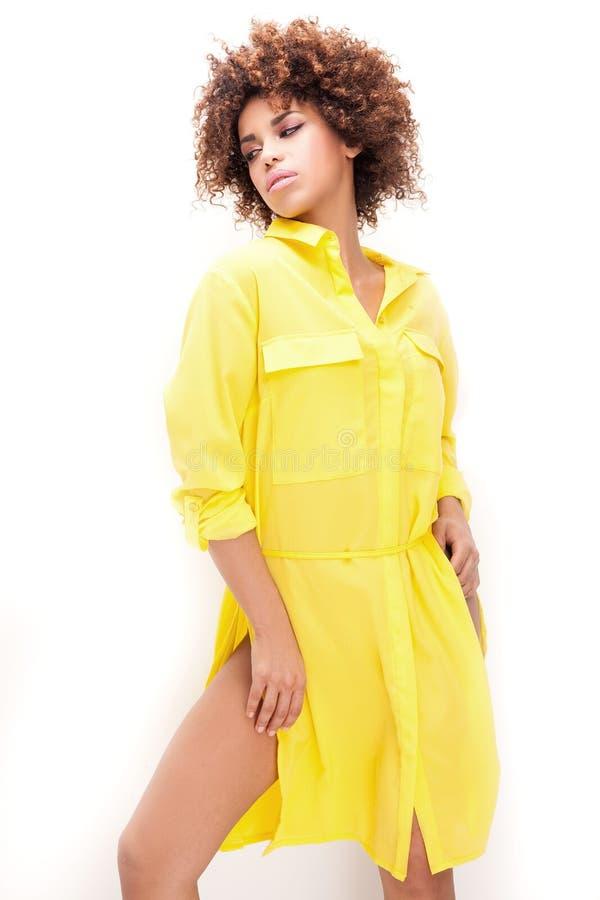 Muchacha con afro en vestido amarillo imagenes de archivo