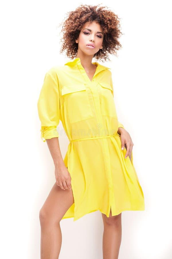 Muchacha con afro en vestido amarillo imagen de archivo