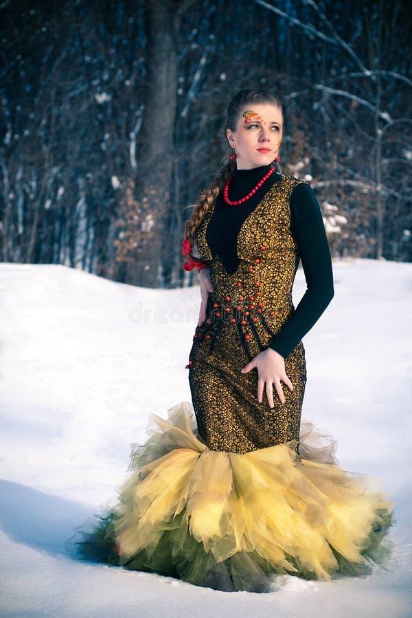 Muchacha con el arte de cuerpo que se coloca en la nieve imagen de archivo libre de regalías