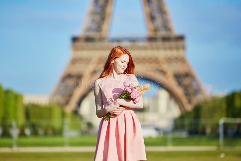 Muchacha con el baguette del pan francés y las flores tradicionales delante de la torre Eiffel fotografía de archivo libre de regalías