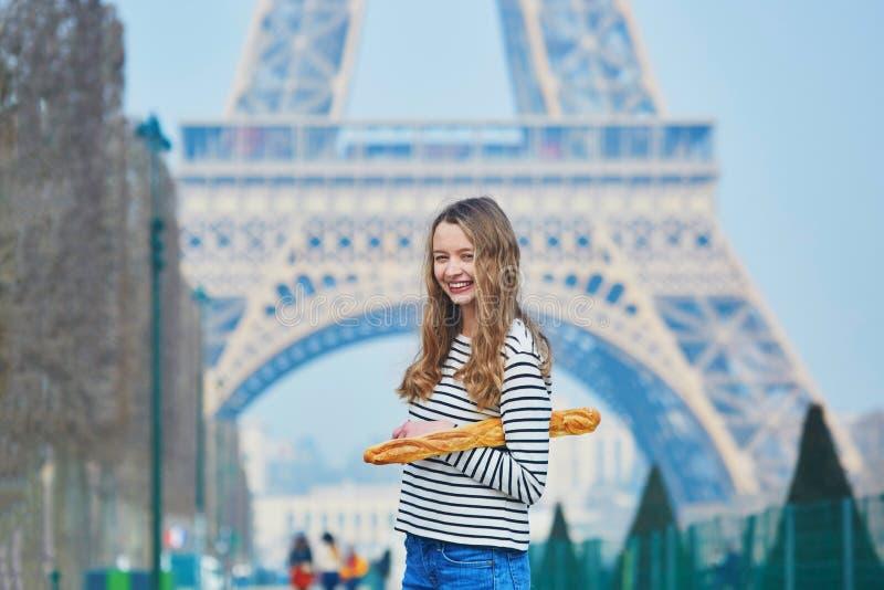 Muchacha con el baguette francés tradicional cerca de la torre Eiffel fotos de archivo libres de regalías