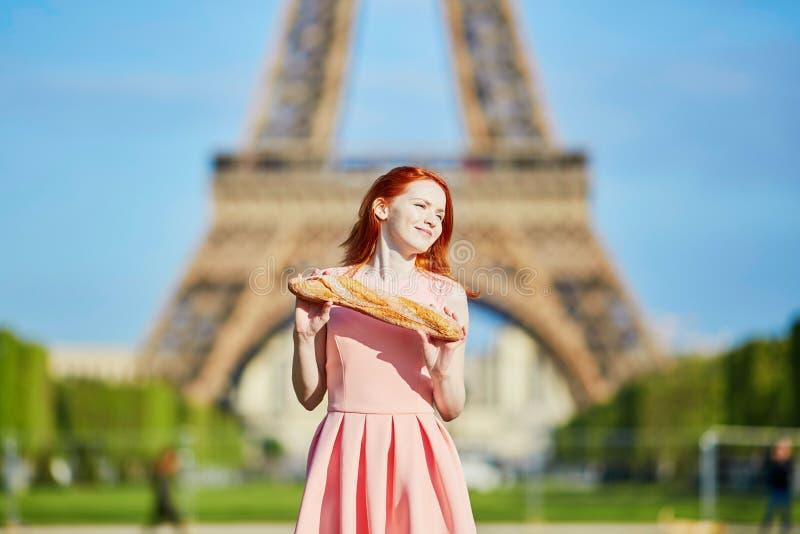 Muchacha con el baguette tradicional del pan francés delante de la torre Eiffel imagen de archivo