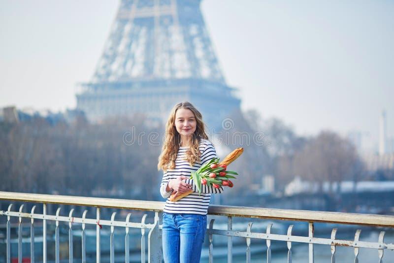 Muchacha con el baguette y los tulipanes franceses tradicionales imagenes de archivo