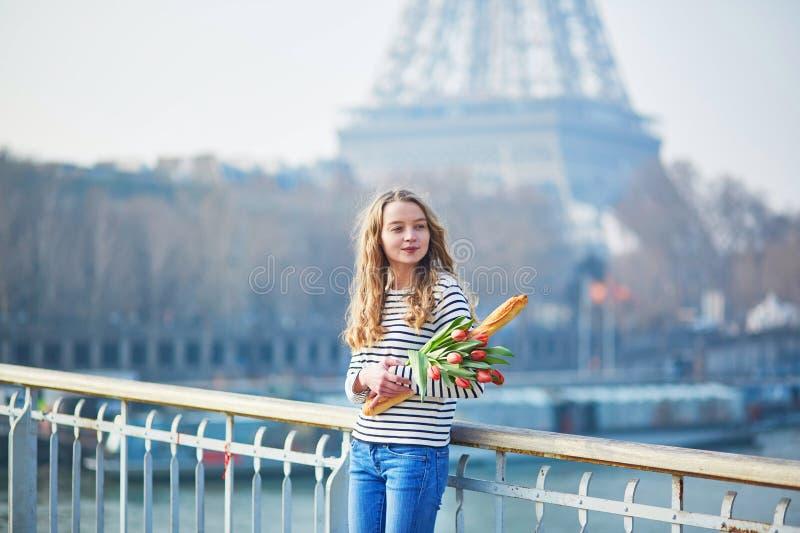 Muchacha con el baguette y los tulipanes franceses tradicionales fotografía de archivo
