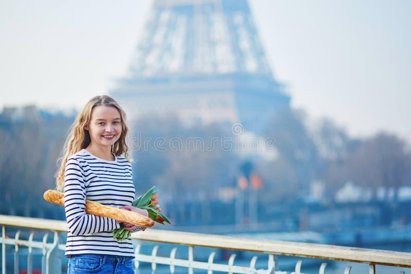 Muchacha con el baguette y los tulipanes franceses tradicionales imagen de archivo