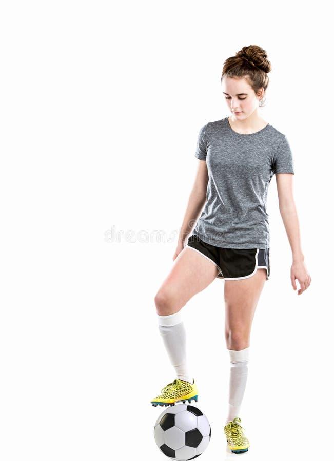 Muchacha con el balón de fútbol que lleva la ropa atlética incluyendo los zapatos del fútbol foto de archivo libre de regalías