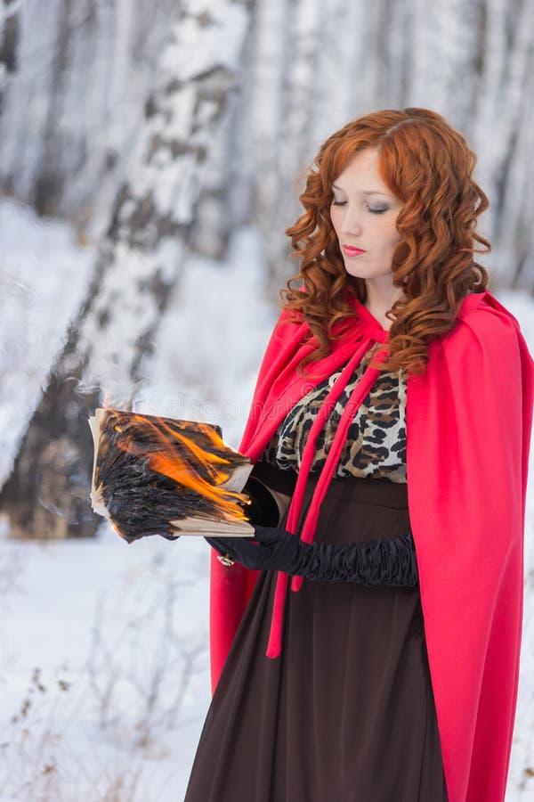 Muchacha con el burning de libro imagen de archivo