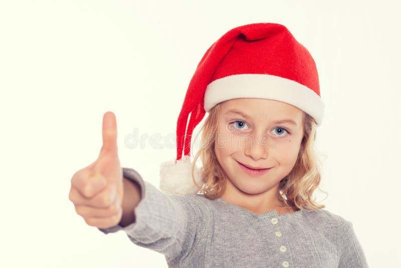 Muchacha con el casquillo y el pulgar de Papá Noel para arriba imagenes de archivo