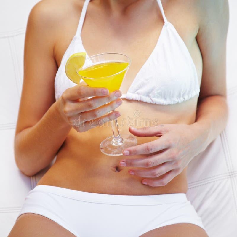 Muchacha con el coctel amarillo en verano foto de archivo libre de regalías