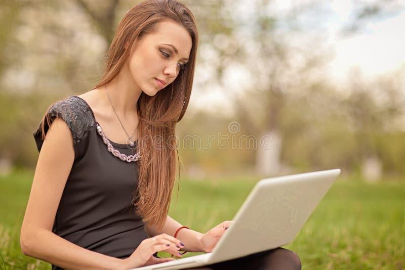 Muchacha con el cuaderno blanco en césped verde foto de archivo