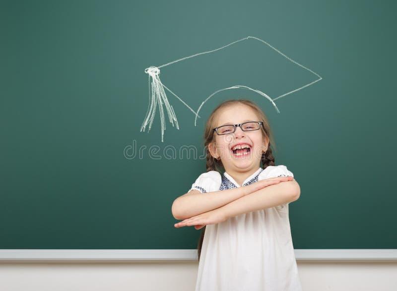 Muchacha con el dibujo académico del casquillo en consejo escolar fotografía de archivo libre de regalías