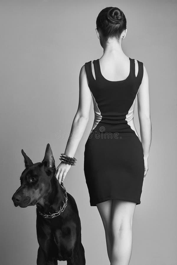 Muchacha con el doberman Mujer joven hermosa con el perro imágenes de archivo libres de regalías