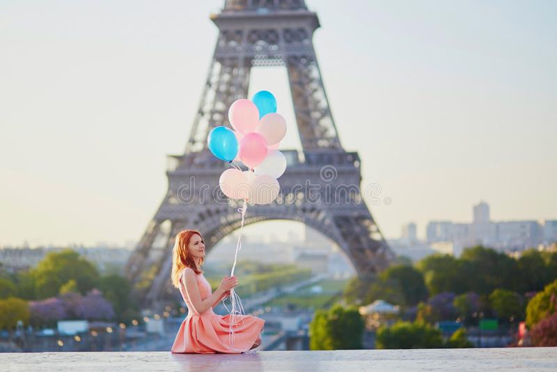 Muchacha con el manojo de globos delante de la torre Eiffel en París imagen de archivo
