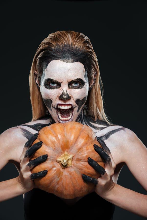 Muchacha con el maquillaje esquelético asustado que lleva a cabo la calabaza y el grito fotografía de archivo