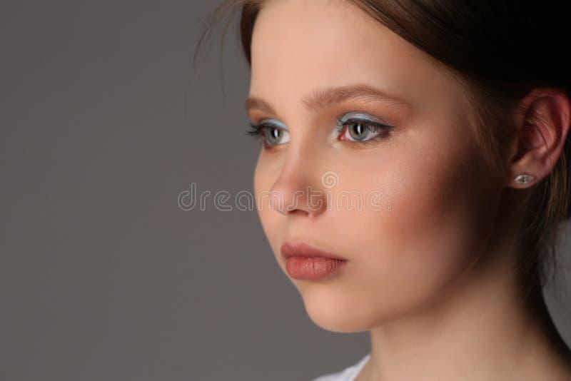 Muchacha con el maquillaje que mira lejos Cierre para arriba Fondo gris fotos de archivo libres de regalías