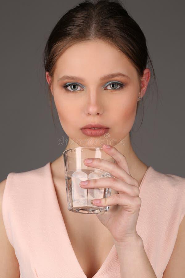 Muchacha con el maquillaje que sostiene el vidrio de agua Cierre para arriba Fondo gris imágenes de archivo libres de regalías