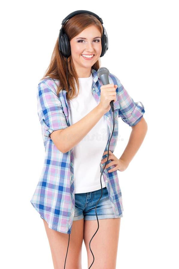 Muchacha con el micrófono y los auriculares foto de archivo