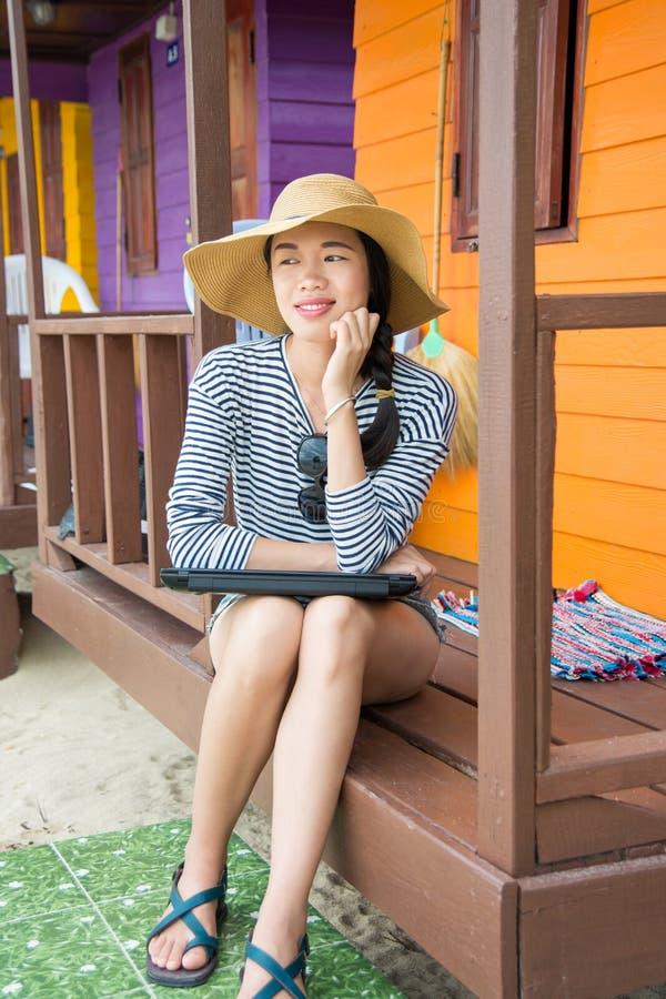 Muchacha con el ordenador portátil delante de una casa de playa fotografía de archivo