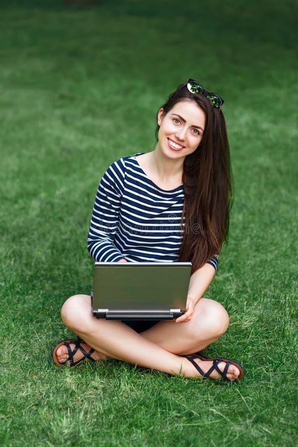 Muchacha con el ordenador portátil en hierba fotos de archivo