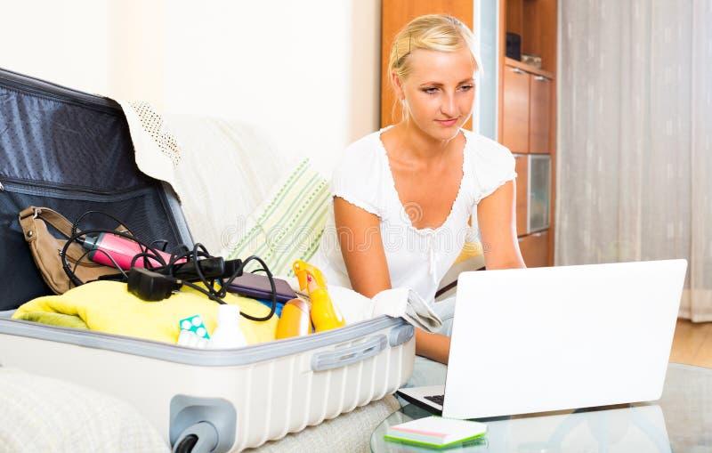 Muchacha con el ordenador portátil y el equipaje foto de archivo