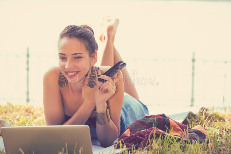Muchacha con el ordenador portátil y el teléfono móvil al aire libre imágenes de archivo libres de regalías
